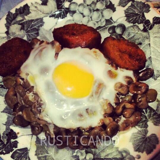 Un plato de huevos fritos con habas y pan mojado en grasa del chorizo. Comida de viña